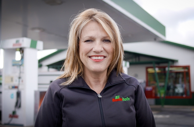 A smiling woman in front of a gas station